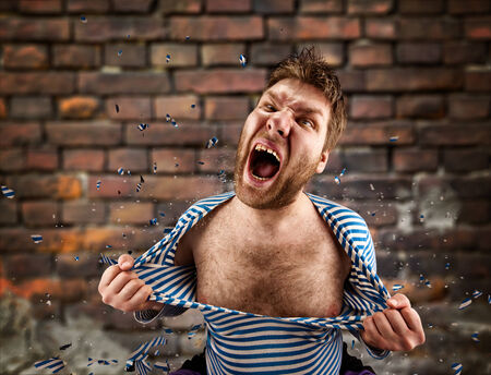 Angry man is tearing clothing on himself outdoors photo