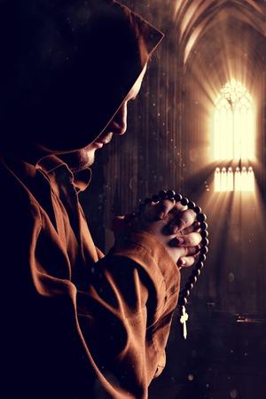 Monnik in gewaad met twee handen geklemd in gebed in de kerk