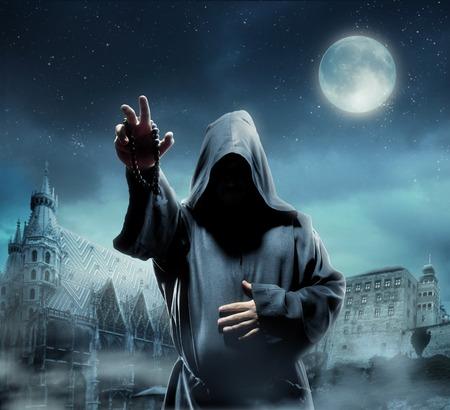 moine: Moine médiéval contre l'église la nuit