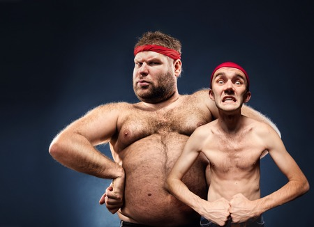Funny fat and thin body builders show their muscles Stock Photo