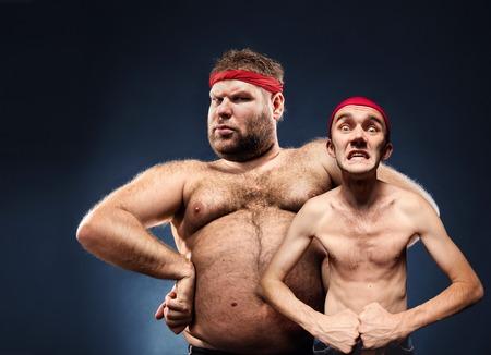 desnuda: Grasa y el cuerpo delgado constructores divertidos muestran sus m�sculos Foto de archivo