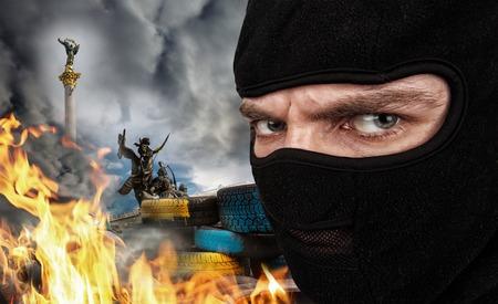 maidan: Serious man in a balaclava mask against burning Ukrainian Maidan