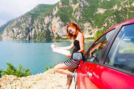Traveler girl is reading a map in mountains photo