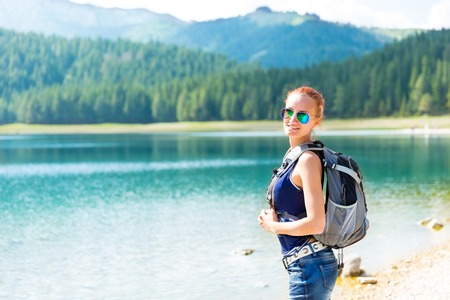 Pretty woman with backpack is walking against blue lake photo
