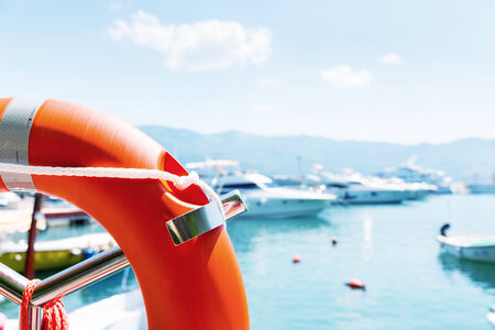 Lifebuoy in sea port against yachts at summer day photo
