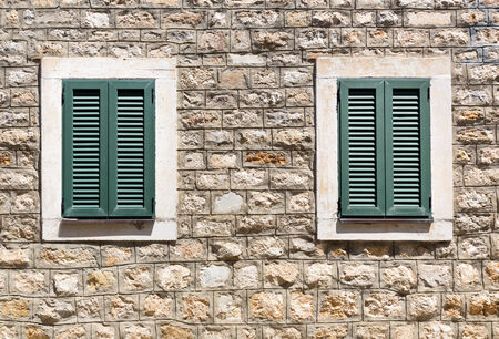 Old wooden windows in a stone wall