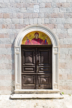 arched: Arched old wooden door in a church stone wall Stock Photo