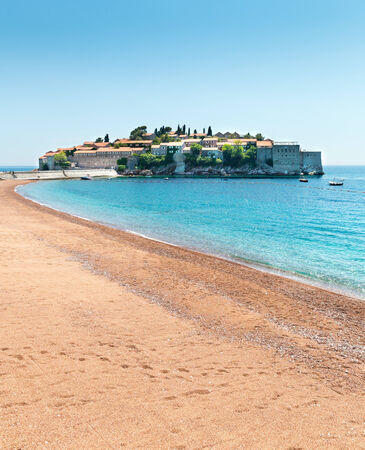 Nice sandy beach against an old town island photo