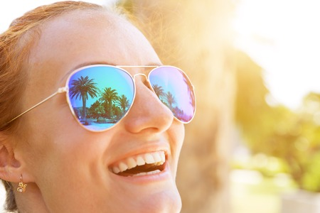 Palm trees reflect in the happy girl sunglasses Stock Photo