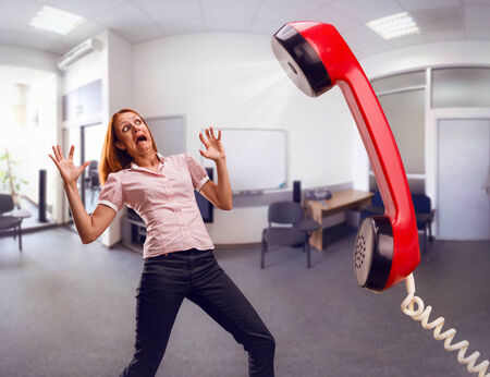 woman screaming: Big phone is screaming to scared woman in office Stock Photo