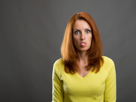 Portrait of beautiful serious redhead woman is teasing with her tongue photo