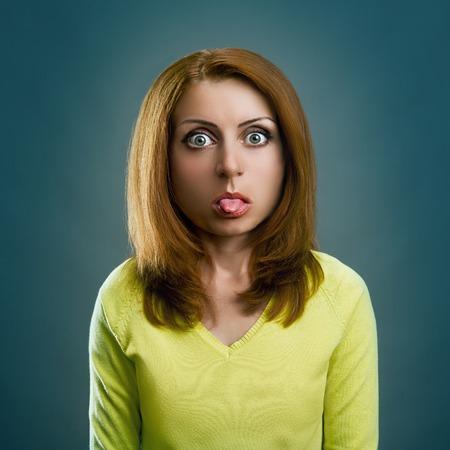 sacar la lengua: Chica Mujer con gran cabeza está pegando hacia fuera la lengua sobre un fondo gris