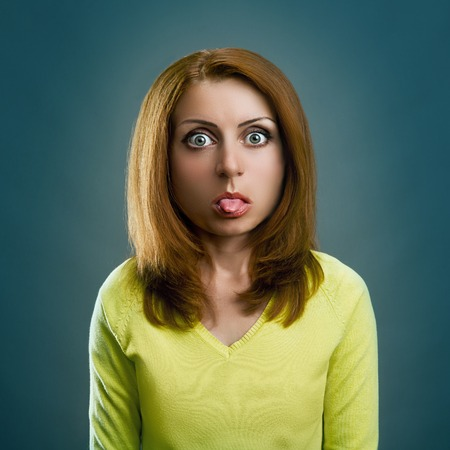 sticking tongue: Woman girl with big head is sticking out her tongue over a gray background Stock Photo
