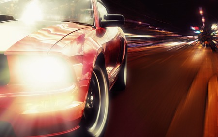 Red sport car closeup picture on a narrow night road Stock Photo