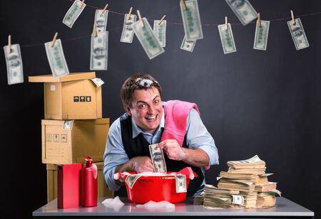 illicit: Happy businessman is laundering money banknotes in foam in red washbowl