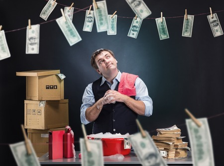 washbowl: Glad businessman is laundering money banknotes in foam in red washbowl Stock Photo