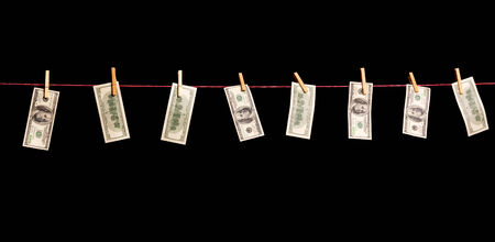 Dollars banknotes are hanging on a rope isolated on black