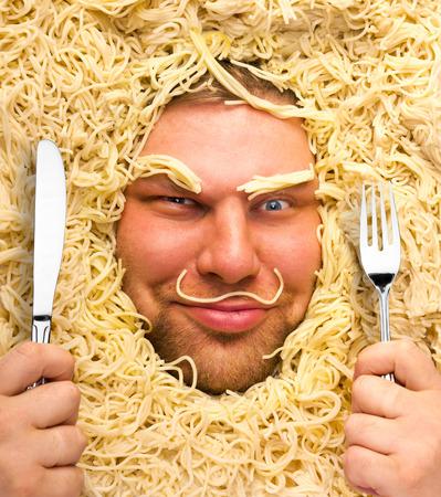hombre comiendo: Hombre divertido con el tenedor y el cuchillo en la pasta