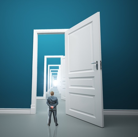 one way: Small businessman is standing in front of long way of opened doors
