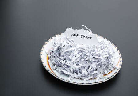 Plate of heap of white shredded papers and paper with agreement photo