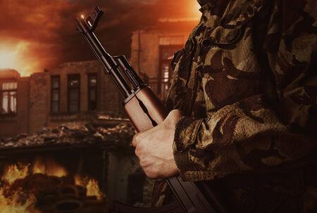 Soldier is holding gun on apocalyptic dark background photo