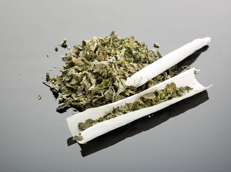 tar paper: Handmade cigarette with dried marijuana on gray background