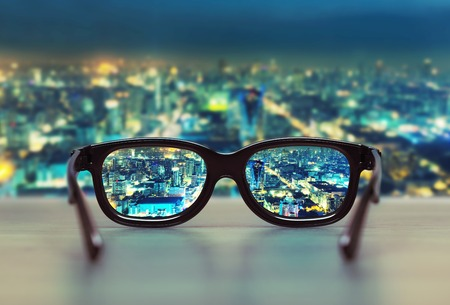 viewpoint: Night cityscape focused in glasses lenses. Vision concept