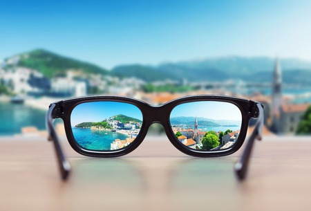 visions: Cityscape focused in glasses lenses. Vision concept Stock Photo
