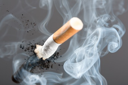 cigarette smoke: Cigarette butt with thick fume, studio picture