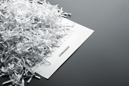 Big heap of white shredded papers on list with agreement