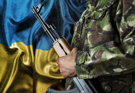 Military man over Ukraine waving flag photo