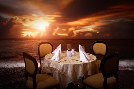 Evening beach dinner serving table in sunset light photo