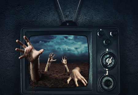 coming out: Zombie hand coming out of his grave from TV,halloween night Stock Photo