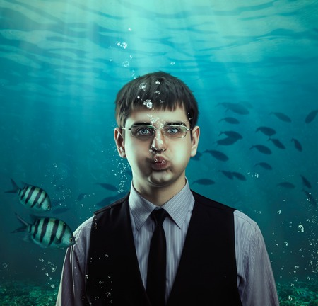 Underwater scene of a businessman with fishes, business concept Stock Photo