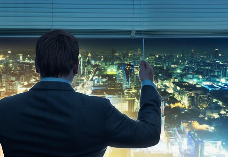 looking through window: Businessman is looking through the window with night city view
