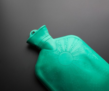 hottie: Green rubber hot water bottle on a gray background Stock Photo