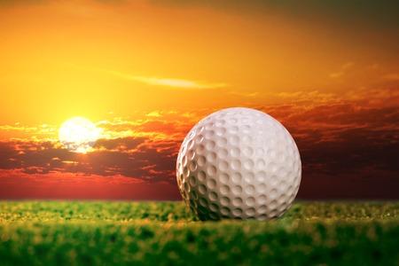 cielo atardecer: Pelota de golf en el c�sped en el atardecer luces