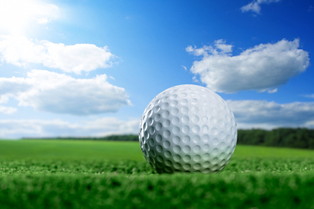Golf ball is lying on green lawn against blue sky