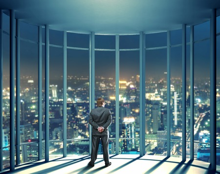 view through: Businessman is standing in front of night view of buildings from the last floor of high office building