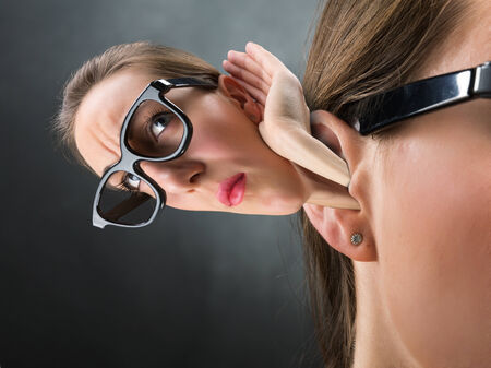 big ear: Woman listening with other woman from her ear, humor concept