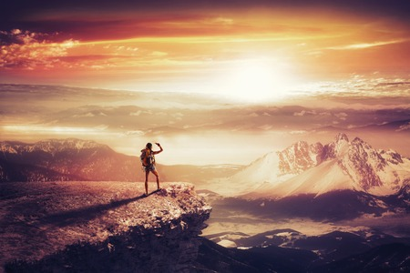 Pretty traveler woman with backpack on the top of mountain looking at sunset Stockfoto