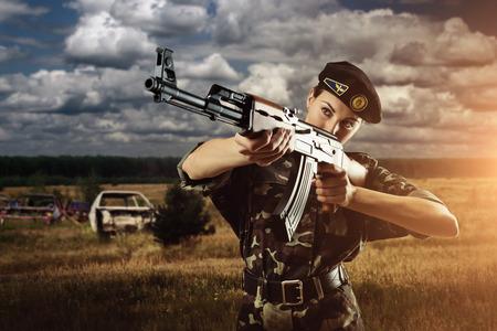 filmacion: Mujer soldado del Ejército está disparando en el campo de batalla