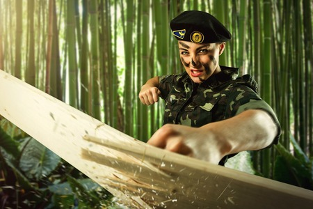military training: Strong army soldier woman is hiting wooden board
