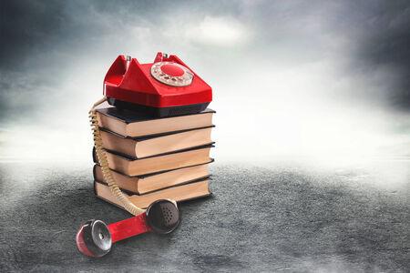 suspenso: Teléfono rojo de la vendimia en un camino brumoso Foto de archivo