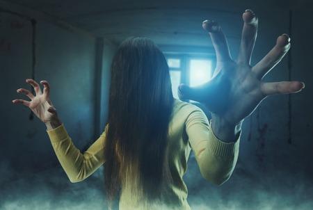 버려진 된 건물에 그녀의 얼굴에 긴 머리를 가진 좀비 소녀
