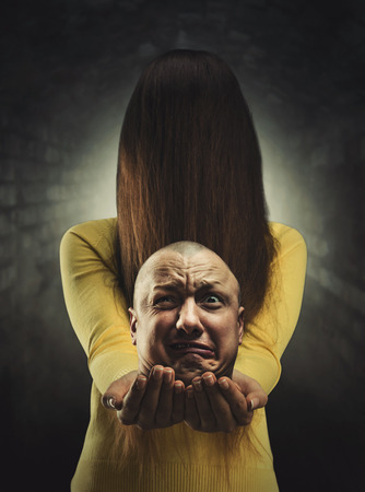 deadman: Zombie girl with long hair in her face in holding a head of deadman Stock Photo