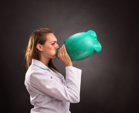 Medical woman worker is inflating a water warmer photo