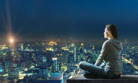De vrouw zit op het dak met mooi verlichte uitzicht op de stad 's nachts Stockfoto