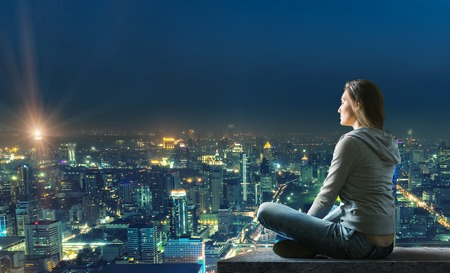 Woman is sitting at the housetop with nice illuminated city view at night Stock Photo