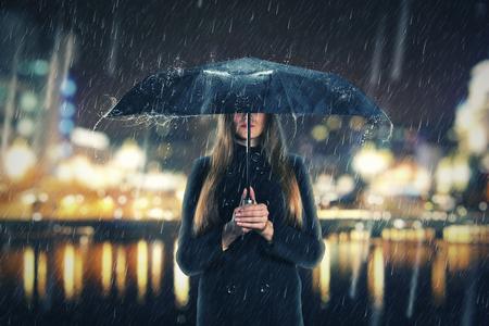 sotto la pioggia: La donna è in piedi sotto la pioggia con un ombrello nero di notte Archivio Fotografico
